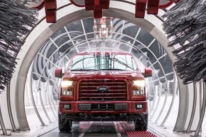 Red truck exiting Tommy Car Wash Tunnel